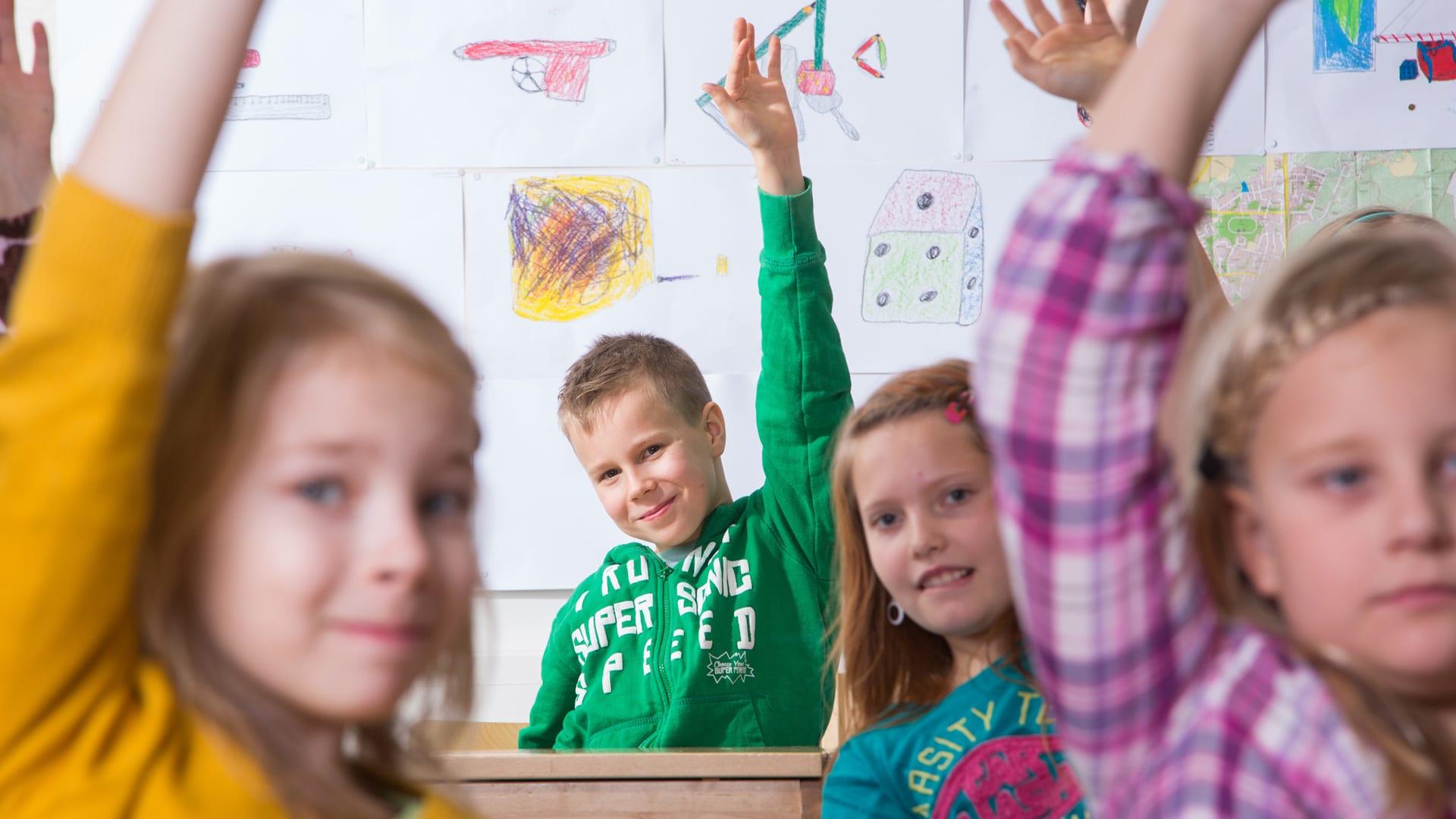 Lapset viittaavat oppitunnilla.